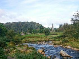 Irland: Wald und Wiese mit typischem Steinturm und Fluss