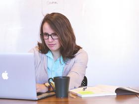 Frau am Laptop mit Kaffeetasse