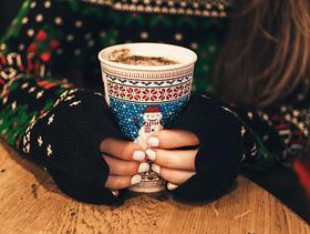 Nahaufnahme auf Hände, die einen weihnachtlichen Becher halten