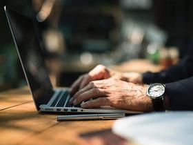 Nahaufnahme von männlichen Händen am Laptop