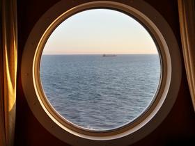 Sicht aus einem Bullauge auf das Meer