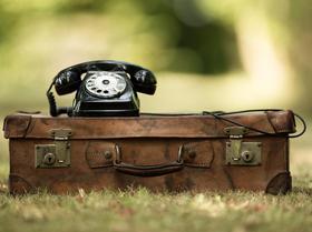 Telefon auf Koffer im Grünen