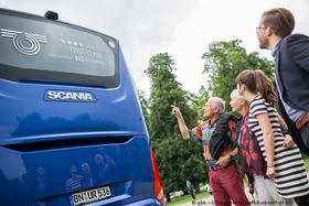Bus von hinten und 3 Menschen davor