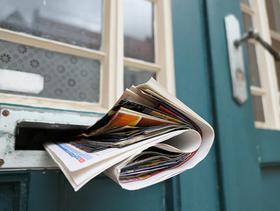 Zeitung im Briefkasten in einer blauen Tür