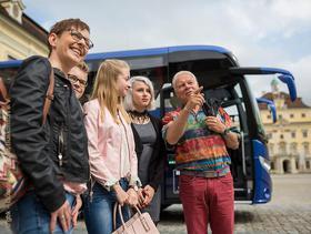 Gruppe steht vor blauem Reisebus auf einem Schlossplatz