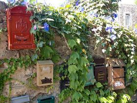Bewachsene Mauer in Liguren mit bunten Briefkästen